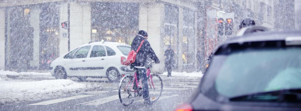 une personne qui se déplace à vélo dans Grenoble en hiver